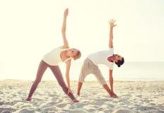 Couple making yoga exercises outdoors Stock Photography