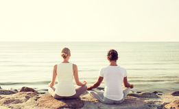 Couple making yoga exercises outdoors Stock Photography