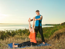 Couple making yoga exercises outdoors Stock Photos