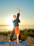 Couple making yoga exercises outdoors Royalty Free Stock Images
