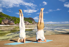 Couple making yoga headstand on mat outdoors Stock Photos
