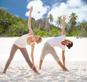 Couple making yoga left triangle pose outdoors Royalty Free Stock Photography