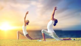 Couple making yoga low lunge pose outdoors Royalty Free Stock Image