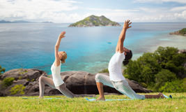 Couple making yoga in low lunge pose outdoors. Fitness, sport, relax and people concept - couple making yoga in low lunge pose over natural background stock image