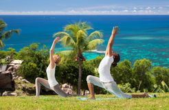 Couple making yoga in low lunge pose outdoors. Fitness, sport, relax and people concept - couple making yoga in low lunge pose over natural background royalty free stock images