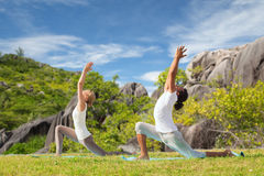 Couple making yoga in low lunge pose outdoors. Fitness, sport, relax and people concept - couple making yoga in low lunge pose over natural background stock photography