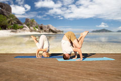 Couple making yoga over tropical beach background Stock Image