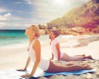 Couple making yoga upward facing dog pose outdoors Royalty Free Stock Photos