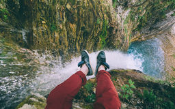 Couple male feet on a rock on a waterfall background. Male Traveler sitting on cliff with waterfall view. Travel Lifestyle adventure vacations concept Stock Photography