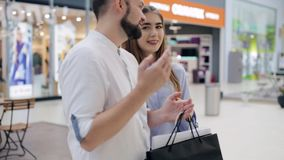 Couple in the mall standing in front of the shop window and talking stock footage