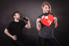 Couple. Man addicted to alcohol. Family and alcoholism problems. Addiction and trouble of drinking. Man with alcohol bottle. Woman holds paper broken heart stock photos