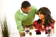 Couple: Man Brings Dinner to Table Royalty Free Stock Photography