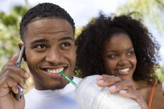 Couple With Man On Call Sipping Milkshake Stock Image