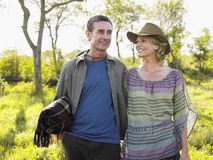 Couple With Man Carrying Blanket On Meadow Royalty Free Stock Images