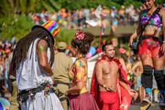 Couple of man with dreadlocks and young woman on the background of blurry man in devil costume and woman walking on stilts royalty free stock photos