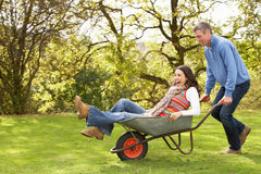 Couple With Man Giving Woman Ride In Wheelbarrow royalty free stock photos
