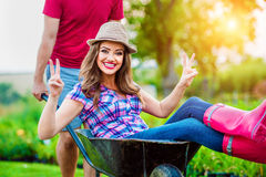 Couple with man giving woman ride in wheelbarrow Stock Images