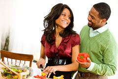 Couple: Man Helps Woman With Salad Stock Photos