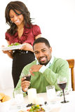 Couple: Man Looking to Camera While Girlfriend Brings Dinner Royalty Free Stock Images
