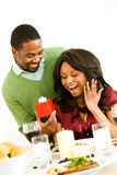 Couple: Man Surprises Woman with Present at Dinner stock photo