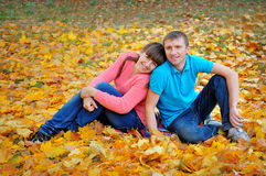 Couple man and woman in autumn yellow leaves. Couple men and women in autumn yellow leaves royalty free stock photo