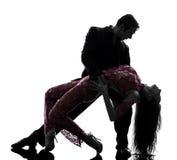 Couple man woman ballroom dancers tangoing  silhouette. One caucasian couple men women ballroom dancers tangoing  in silhouette studio  on white background Stock Photos