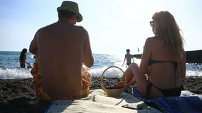 Couple man and woman in bathing suits, eating fruits and berries on a sea beach on a background of waves stock footage