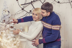 Couple man and woman in a Christmas interior with a fir tree Royalty Free Stock Photo