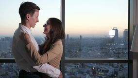 Couple, man and woman are dancing near the panoramic window with city view. Couple in love, young man and woman in office suit are dancing. They are near the stock footage