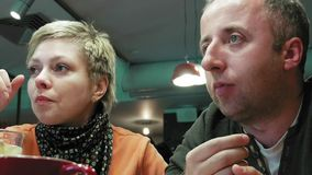 Couple man and woman eats talks in cafe restaurant stock video