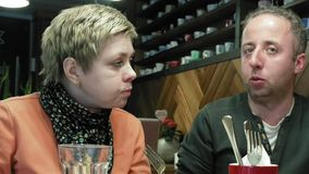 Couple man and woman eats talks in cafe restaurant stock video footage