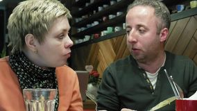 Couple man and woman eats talks in cafe restaurant stock footage