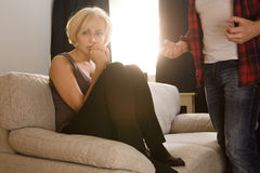 Couple man and woman having conflict at home. Couple men and women having conflict concerning family life. Frightened blond lady sitting on sofa or couch and Royalty Free Stock Photo