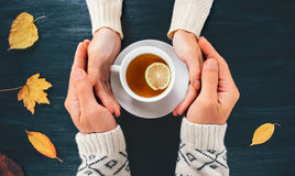 Couple Man and Woman in Love holding hands. With hot tea lemon cup on dark wooden table with autumn leaves Romantic relationship feelings concept top view Royalty Free Stock Photography