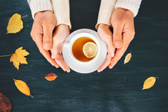 Couple Man and Woman in Love holding hands. With hot tea lemon cup on dark wooden table with autumn leaves Romantic relationship feelings concept top view Royalty Free Stock Images