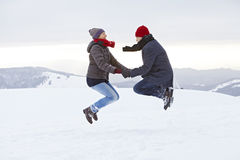 Couple Man Woman mountain winter snow jump Stock Image