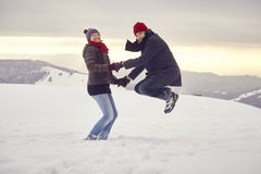 Couple Man Woman mountain winter snow jump Royalty Free Stock Photo
