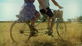 Couple man and woman riding a bicycle tandem on summer field and haystacks