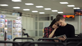 Couple, man and woman sitting in waiting room and look in tablet. They are going on a vacation bought tickets and await announcement of start of boarding. But stock video footage