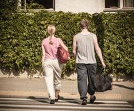 Couple man and woman with sport bags. Couple men and women with sport gym bags crossing pedestrian crosswalk outdoor. Active young girl and guy in training suit Royalty Free Stock Images
