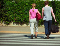 Couple man and woman with sport bags. Couple men and women with sport gym bags crossing pedestrian crosswalk outdoor. Active young girl and guy in training suit Stock Photography