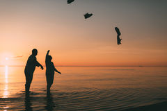 Couple of man and woman standing in the sea and throw your shoes at the beach. Royalty Free Stock Photo