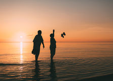 Couple of man and woman standing in the sea and throw your shoes at the beach. Stock Photography