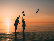 Couple of man and woman standing in the sea and throw your shoes at the beach. Royalty Free Stock Photography