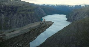 Couple Man and Woman on Trolltunga cliff mountains Love and Travel. Emotions Lifestyle concept. Young family traveling together active adventure vacations in stock video