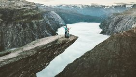 Couple Man and Woman on Trolltunga cliff raised hands mountains. Love and Travel emotions Lifestyle concept. Young family traveling together active adventure Stock Image