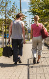 Couple man and woman walking with sport bags. Couple men and women with sport gym bags walking outdoor. Active young girl and guy in training suit sportswear Stock Photo