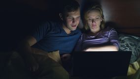 Couple, man and woman, watching a movie on a laptop on a bed in the bedroom before bed. watching an exciting movie, the