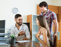 Couple and manager talking about purchase in the office Stock Images