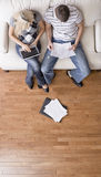Couple Managing Personal Finances. High angle view of young couple sitting on a couch with a laptop and paperwork. Vertical shot Royalty Free Stock Images